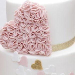 Білий торт з безліччю маленьких сердечок і одним великим