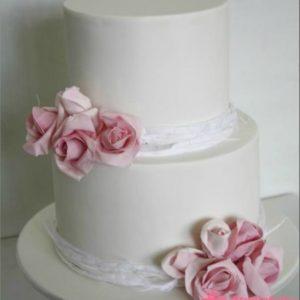 Гладкий білий торт з рожевими квітами і стрічками