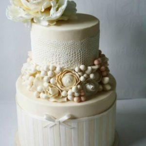 Мастиковий торт з прикрасою і великою квіткою на вершині