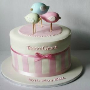 Розово-белый торт с бантом и фигурками птичек