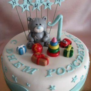 Білий тортик з блакитною прикрасою і фігурками на ньому