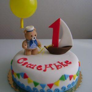 Белый торт с гирляндой, парусником и медвежонком-матросом