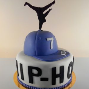 Білий торт з написом «Hip-Hop», кепкою зверху і аплікацією хіп-хопера