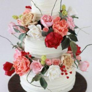 Білий торт з безліччю квітів з мастики