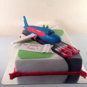 Торт з фігуркою літака на злітній смузі