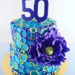 Торт украшенный колечками и огромным цветком