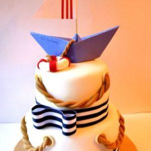 Білий торт зі смугастими стрічками і вітрильником зверху