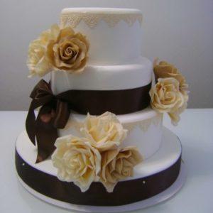 Білий торт з коричневою окантовкою і квітами