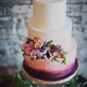 Торт з фіолетовою основою прикрашений букетом квітів