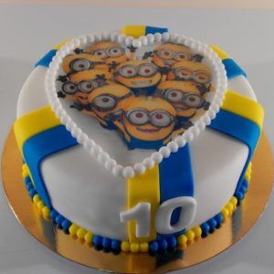 Білий торт з жовто синіми смужками і міньйонами