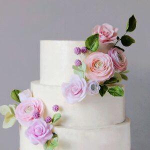 Білий триярусний торт з квітами на весілля