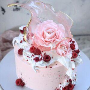 Розовый торт украшенный малиной и цветком