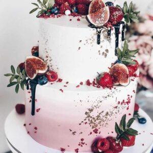 Двох'ярусний біло-рожевий торт прикрашений ягодами