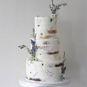Трехъярусный торт украшенный белым кремом
