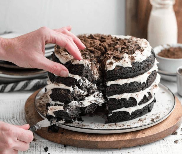 Женщина отрезает кусочек торта