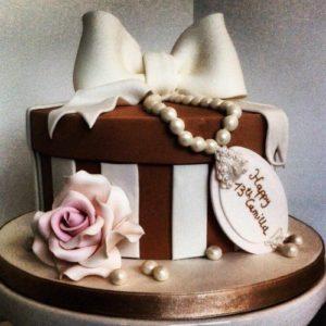 Коричнево-белый торт с нежно розовой розой с белым бантиком