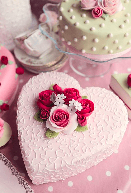 розовый торт в форме сердца украшенный цветами